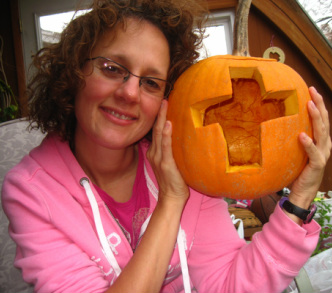 Should Christians celebrate Halloween? Photo of Debra Torres holding a pumpkin with a cross carved in.